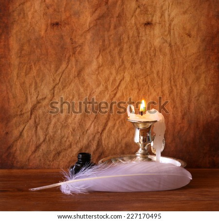 low key image of white Feather, inkwell and burning candle on a wooden table  - stock photo