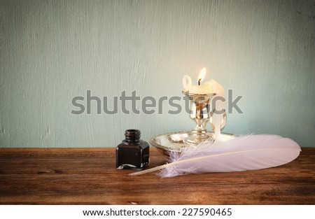 low key image of white Feather, inkwell, and candle on old wooden table. filtered image - stock photo