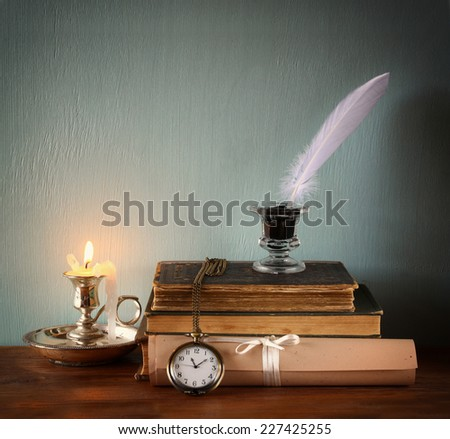 low key image of white Feather, inkwell, scroll ancient books on old wooden table. filtered image - stock photo