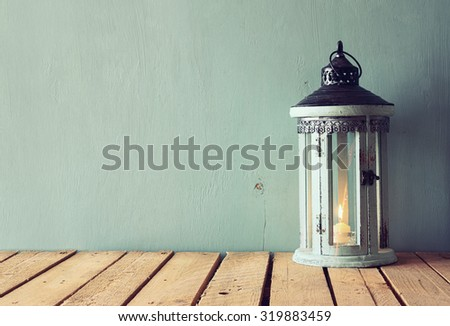 low key image of white wooden vintage lantern with burning candle and tree branches on wooden table. retro filtered image  - stock photo
