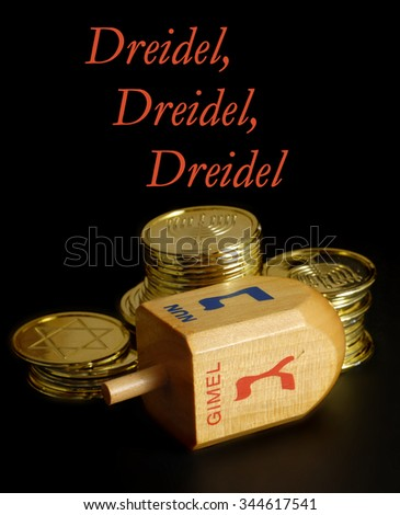 Low key image with side lighting of Hanukkah dreidel and gelt. Objects are on a rough, black background. Gelt has seasonal images of the Star of David and a menorah. Narrow depth of field with text. - stock photo