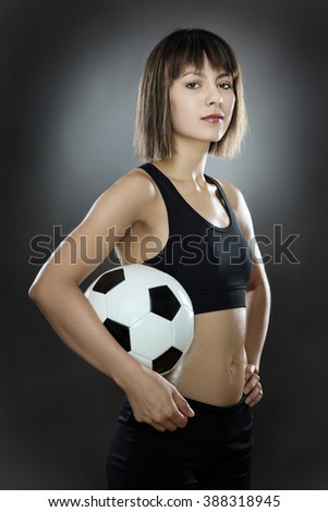 low key lighting of a woman holding a english football shot in the studio on a gray background - stock photo