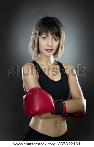 low key lighting of a woman wearing boxing gloves shot in the studio on a gray background