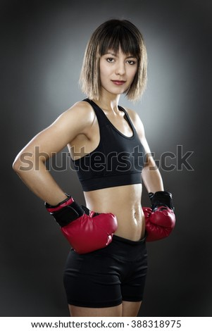 low key lighting of a woman wearing boxing gloves shot in the studio on a gray background - stock photo