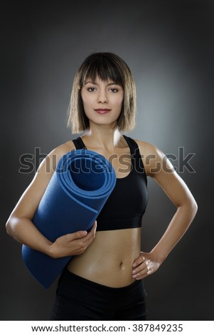 low key lighting of a young woman holding a sports mat shot in the studio on a gray background