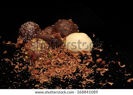 Low Key lighting on a selection of premium chocolates, and chocolate shavings sitting on a black background with space for text - stock photo