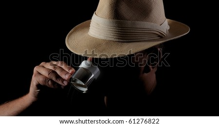 Low-key photo of a hidden man with panama-hat drinking espresso