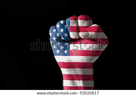 Low key picture of a fist painted in colors of american flag - stock photo