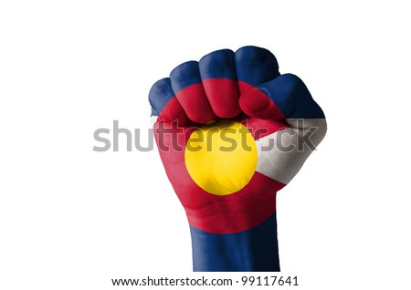 Low key picture of a fist painted in colors of american state flag of colorado - stock photo
