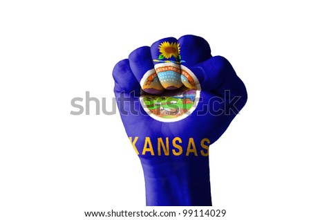 Low key picture of a fist painted in colors of american state flag of kansas - stock photo