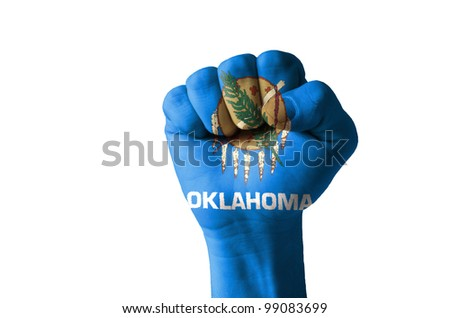 Low key picture of a fist painted in colors of american state flag of oklahoma - stock photo