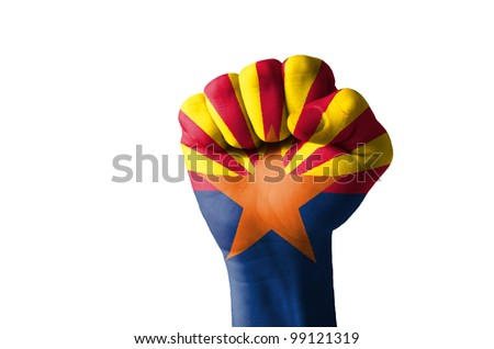 Low key picture of a fist painted in colors of american state flag of wyoming - stock photo