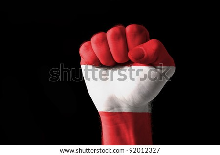 Low key picture of a fist painted in colors of austria flag - stock photo