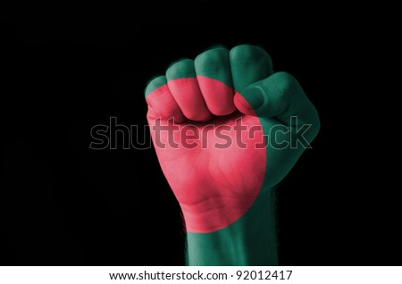 Low key picture of a fist painted in colors of bangladesh flag - stock photo