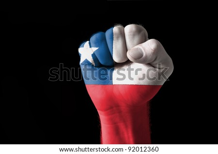 Low key picture of a fist painted in colors of chile flag - stock photo