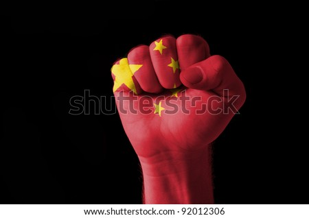 Low key picture of a fist painted in colors of china flag - stock photo