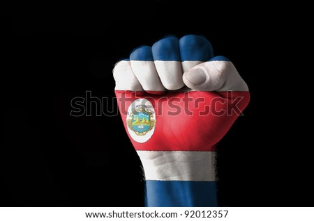 Low key picture of a fist painted in colors of costarica flag - stock photo