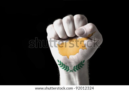 Low key picture of a fist painted in colors of cyprus flag - stock photo