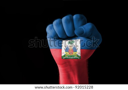 Low key picture of a fist painted in colors of haiti flag - stock photo