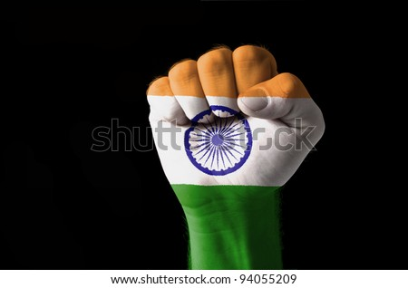 Low key picture of a fist painted in colors of india flag - stock photo