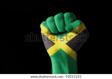 Low key picture of a fist painted in colors of jamaica flag - stock photo