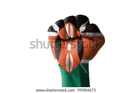 Low key picture of a fist painted in colors of kenya flag - stock photo