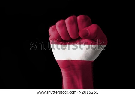 Low key picture of a fist painted in colors of latvia flag
