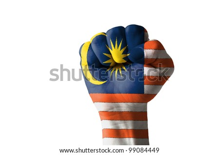 Low key picture of a fist painted in colors of malaysia flag - stock photo
