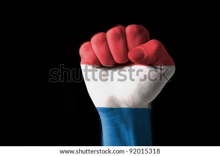 Low key picture of a fist painted in colors of netherlands flag