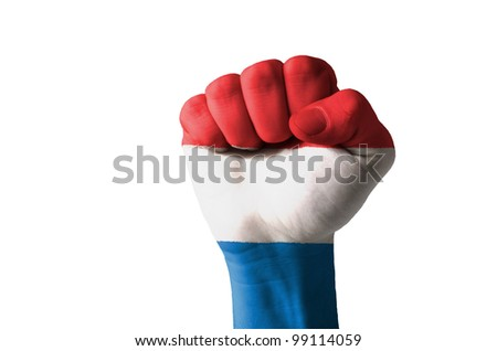Low key picture of a fist painted in colors of netherlands flag - stock photo