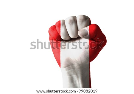 Low key picture of a fist painted in colors of peru flag - stock photo