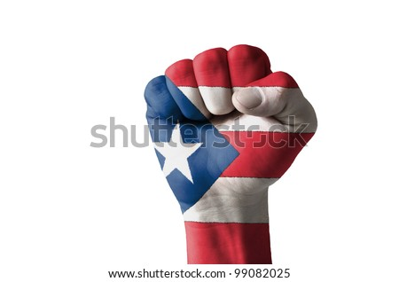 Low key picture of a fist painted in colors of puertorico flag - stock photo