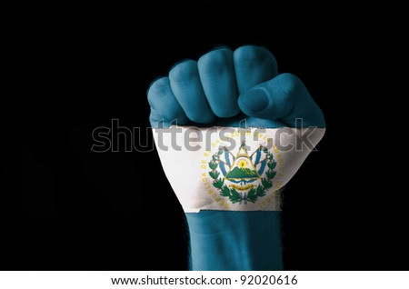 Low key picture of a fist painted in colors of san salvador flag - stock photo