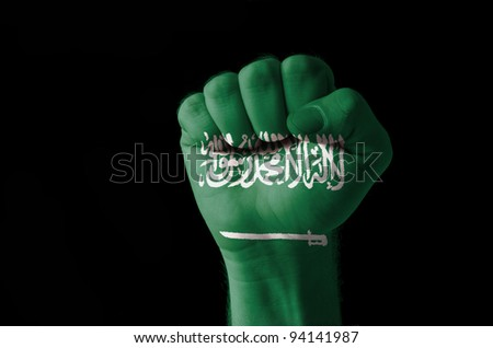 Low key picture of a fist painted in colors of saudi arabia flag - stock photo