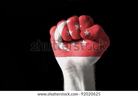 Low key picture of a fist painted in colors of singapore flag