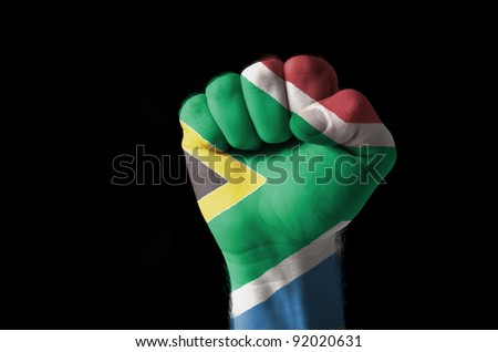Low key picture of a fist painted in colors of south africa flag - stock photo