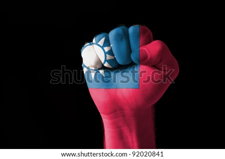 Low key picture of a fist painted in colors of taiwan flag