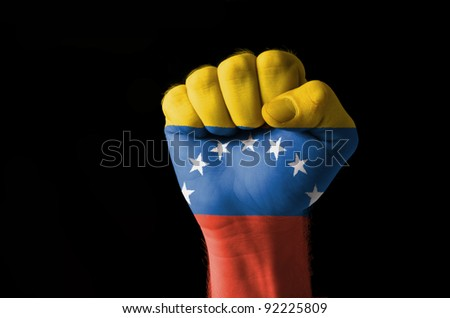 Low key picture of a fist painted in colors of venezuela flag - stock photo