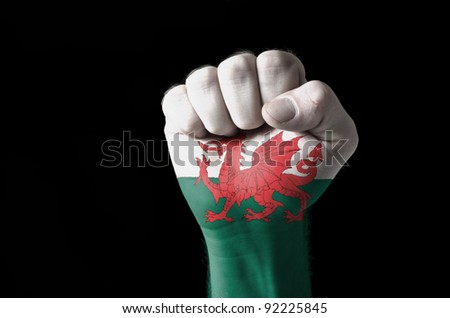 Low key picture of a fist painted in colors of wales flag - stock photo