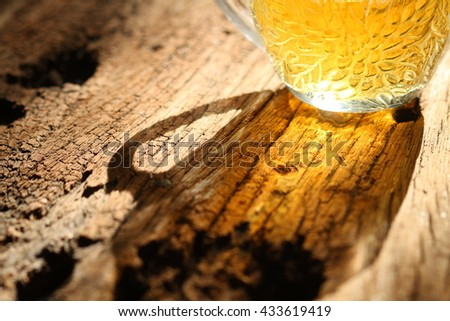 Low key picture, shilouette of tea cup on a wood background. Selective focus
