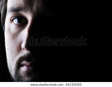 Low-key portrait - half face - serious sad and angry looking man