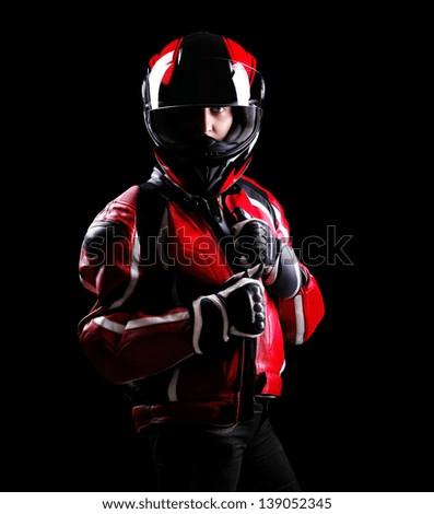 Low key portrait of a girl biker standing on black background - stock photo