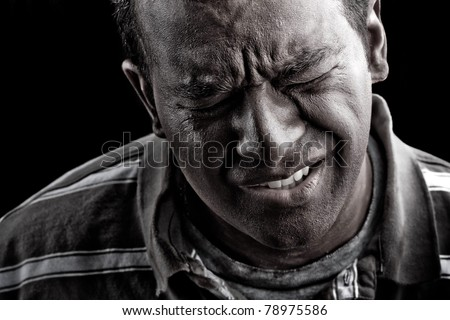 Low key portrait of a man suffering from extreme anguish pain or other hardship over a black background. - stock photo