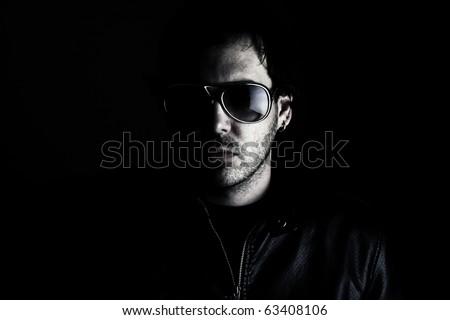 Low-key portrait of a man wearing sunglasses - stock photo