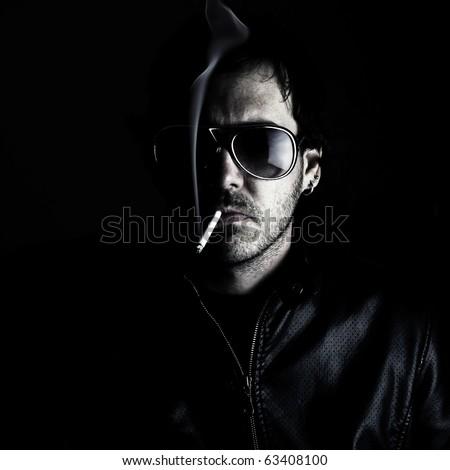 Low-key portrait of a man wearing sunglasses and smoking a cigerette. - stock photo