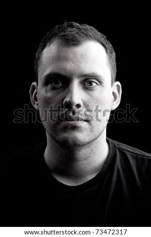 Low key portrait of a serious man in his late twenties in black and white.  Shallow depth of field. - stock photo