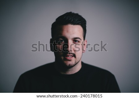 Low key portrait of a serious man in his late twenties slight smile - stock photo