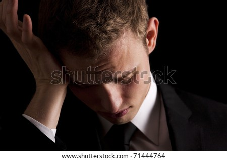 Low key portrait of a young businessman with a migraine or possibly a hangover. - stock photo