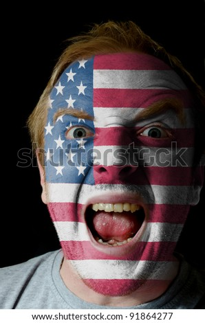 Low key portrait of an angry man whose face is painted in colors of american flag - stock photo