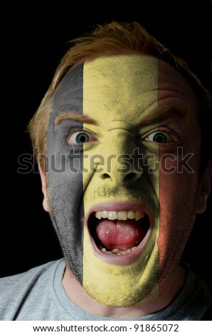 Low key portrait of an angry man whose face is painted in colors of belgian flag